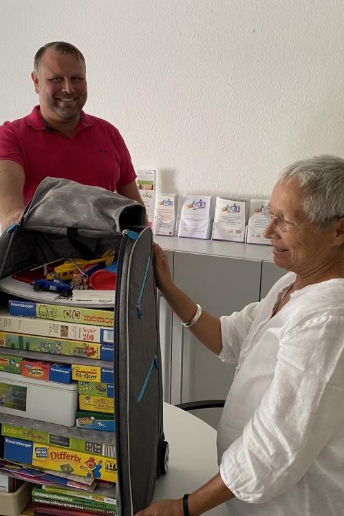 """Zum Abschied schenkt Gudula Kohn - hier bei der Übergabe an Martin Kraus vom Personalamt - gut gefüllt Trolleys für ein """"Eltern-Kind-Büro"""". Foto: TME"""