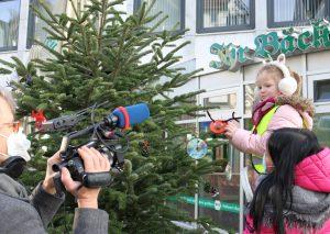 Bildunterzeile: Kamera läuft: Erzieherin Vanessa Neuhaus hebt ein Mädchen hoch, das ein Rentier in die Zweige hängt. Foto: Stadt Mettmann