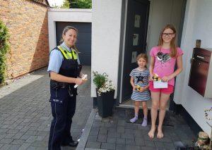 Polizeihauptkommissarin Simone Hakenberg hat die ersten Preise der diesjährigen Mobi-Pass-Verlosung verteilt. Die zehnjährige Frieda Hobes sowie ihre Schwester dürfen sich auf einen Besuch im Wuppertaler Zoo freuen. Foto: KPB Mettmann
