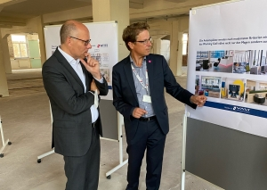Der Bundestagsabgeordnete Peter Beyer (links) zeigt sich beindruckt von den Plänen für die Neugestaltung der WITTE Automotive-Zentrale, die Geschäftsführer Rainer Gölz (rechts) ihm auf der Baustelle der neu angemieteten Fläche vorstellt. Foto: Witte